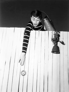 Audrey Hepburn, with purse in hand, reaches for the fence door knob at her Beverly Hills apartment in Los Angeles, 1953. Très Cute!