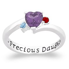 "Celebrate the bond between daughter and parents with this special sterling silver personalized ring. A large heart shaped birthstone represents the daughter's birth month while two small flanking birthstones represent mom and dad. The interior of the ring is inscribed with ""My Precious Daughter"". The birthstones are authentic Austrian crystals and hand implemented."
