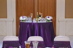 The Sweetheart table from a Wedding Reception held in our Grand Ballroom with seating for 280 guests. Featuring ceiling draping and a crystal chandelier! Accenting the room with fresh floral arrangements and and color palette of plum, silver & white!