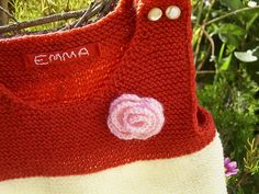 gestrickter Babystrampler mit Häkelblüte