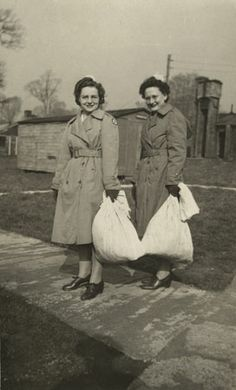 "Alice C. Boehret (US Army Nurse Corps) and her friend ""Wash"" carry bags of clothing on laundry day while posted in Wraxel, England, in late 1944 or early 1945. And they even did the laundry in style! ~"