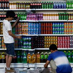 Chinese artist Liu Bolin is painted to blend into rows of drinks in his artwork entitled 'Plasticiser,' to express his helplessness at the use of food additives, in his studio at the 798 Art District in Beijing, China