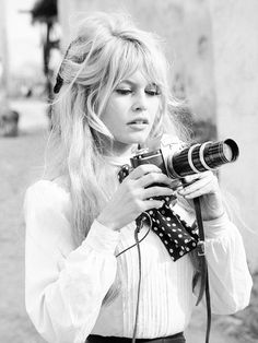 Brigitte Bardot wears a white blouse with a polka dot neck tie and high-waisted pants