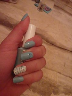 turquoise nail art design with bows and lines