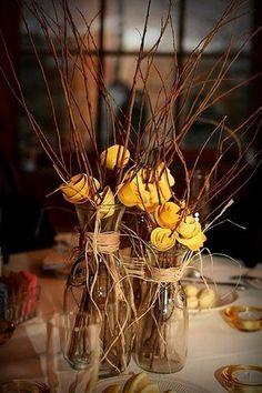 different sizes of vases/mason jars with twigs/sticks and a pop of color (change color for wedding colors)