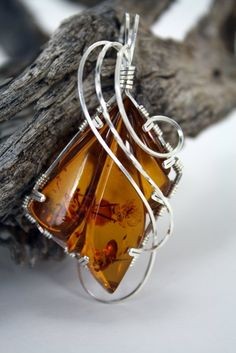 Chosen for its beautiful color, this translucent Amber stone is wrapped in sterling silver. Our design is tailored to the individual stone