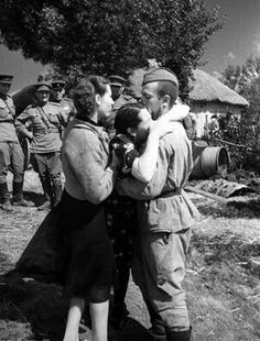 Soviet soldier is hugged by his sister.