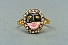 1800 ring from England or Italy depicts an enameled, masked face, with rose-cut diamond eyes and a border of even more rose-cut diamonds set in silver on gold.