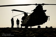 Royal Air Force technicians work on a Chinook helicopter during a…