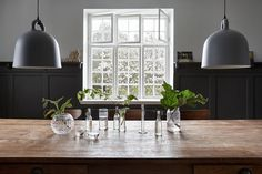 Bell pendant lights by Normann Copenhagen and a simple splash of green on the dining room table.