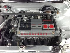 This NES controller car engine is inside a 1989 Honda Civic. It looks so real, but it's really just a painting of a controller on top of the car engine. Honda Civic, Honda S2000, Nintendo Game, Nintendo Controller, Golf 1 Cabrio, Civic Hatchback, 8 Bits, Mitsubishi Lancer Evolution, Ae86