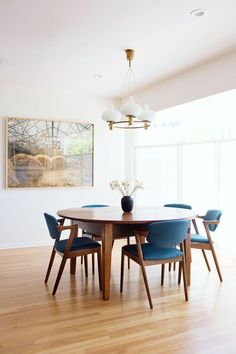 Mid-century modern dining room design minimalist style featuring a large framed photo artwork, vintage modern white glass and brass chandelier, a round table, and blue upholstered chairs - Dining Room Ideas & Decor