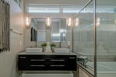 Because this master bathroom lacks much natural light, architect and designer Luciana Corwin employed light colors and strong contrasts to keep the space bright and interesting. Clean, sleek lines give the room a contemporary aesthetic.