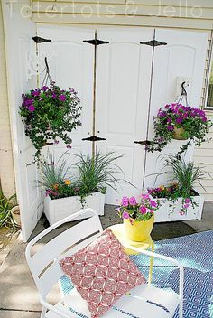 Hinged old panel doors repurposed into a lovely screen and old corbels repurposed into hangers for plants. What's not to like??