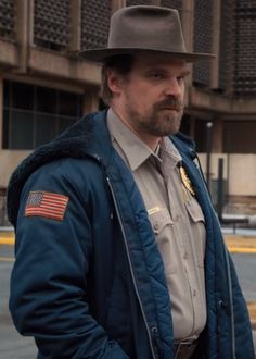 Jim hopper, portrayed by david harbour, is a major character in the first and David Harbour Stranger Things, Joyce Stranger Things, Hopper Stranger Things, Stranger Things Characters, Stranger Things Netflix, Stranger Things Season, Blue Hoodie, Hoodie Jacket, David Harbor