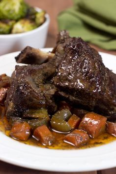 Slow Cooker Braised Short Ribs - This is the ultimate paleo & gluten-free comfort food. Seared beef short ribs simmer in a slow cooker in a beautiful red wine sauce until the meat is so tender and juicy it literally falls right off the bone. #paleo #glutenfree #dairyfree