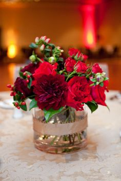 Low centerpieces of burgundy dahlias, red roses and red hypericum berries