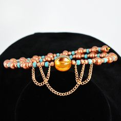 You'll make an unforgettable entrance wearing this retro copper and turquoise glass chain Art Nouveau choker. Or make someone special smile with a gift of this striking classic color combination. The choker features shimmering copper Indian glass and delicate chain, 4mm turquoise cathedral cut Czech glass and a translucent copper Czech glass melon bead. It's a striking one-of-a-kind find. Memory wire is easy to wear and care for. It expands to fit all without losing its shape.  The Sm...