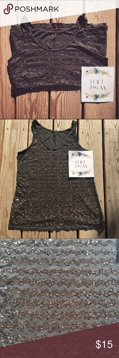 """LOFT Medium Charcoal With Sequin Detail Tank LOFT dark charcoal tank (slight heather quality) with bronze/ dark gold sequin detailing. Sequins in horizontal """"squiggle"""" pattern; starts w/ thin application & squiggles become gradually thicker further down the tank. Worn once. Should comfortably fit size 12-16 (I'm 5'6"""", pear-shaped & wore it when I was in between a 14 and 16). Please feel free to ask questions, additional pics, etc. Easy """"going out"""" shirt- can be casual or dressy. Looks great…"""