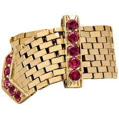 """Cartier Ruby Gold Buckle Ring. """"Buckle Up"""" in style with this Cartier, circa 1945, buckle ring. Designed with a 14 karat yellow gold stacked mesh pattern, the ring is movable and adjustable in size. Buckle loop and mesh tip are mounted with a total of 10 round cut Burmese color rubies."""