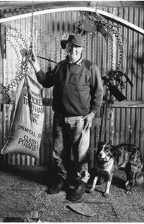 Black and white image of a farmer standing in an old shed with his dog. The farmer is suporting a hanging bag of potatoes.