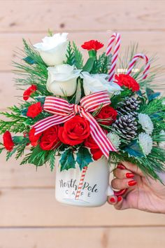 Warm their hearts with this spirited holiday bouquet, arranged in a hand-painted, delightfully oversized mug from the North Pole Café! It's food safe for years of seasonal sipping delight. This bouquet includes red spray roses, miniature red carnations, white button spray chrysanthemums, flat cedar, white pine, and variegated holly. Delivered in Teleflora's Send a Hug® North Pole Café Mug.