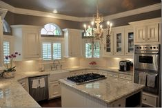 kitchen with white cabinets, white and light gray granite counters, chandelier, gray walls, farmhouse sink, stainless appliances