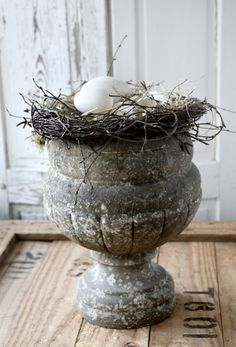 I S A B E L L A S | Byg en rede i stuen: Gamle sandstenskrukker er moderne og kan sagtens bruges indenfor. Her har vi pyntet en sandstenskrukke med grene af hængebirk formet som en rede og bundet sammen med vindseltråd. I reden ligger mos og forskellige udpustede æg.