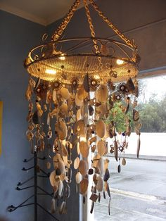 Upside down garden table decorated with strings of shells picked up from Western Cape beaches, glass & wooden beads, electrical motor components, stones and feathers.  Strings constructed with hemp covered wire.
