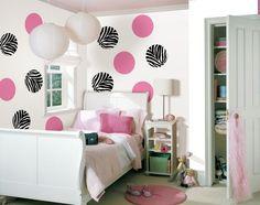 des murs blancs à pois roses et à motifs de zèbre dans la chambre de fille ado