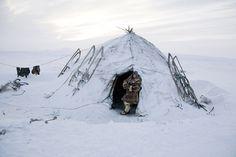 Vitya Nutetgevev, a young Chukchi reindeer herder stands in the doorway of a Yaranga (traditional tent). Chukotskiy Peninsula, Chukotka, Siberia, Russia © Bryan and Cherry Alexander / LUZphoto
