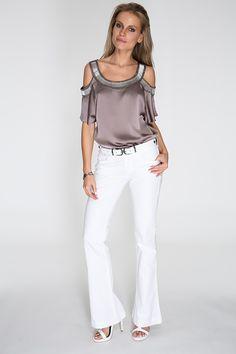 Blusa fendi com recorte nos ombros e aplicação de canutilhos no decote e nas mangas. A calça branca flare e o cinto de duas fivelas complementam o look sofisticado, a cara da mulher Siberian.