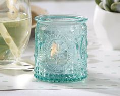Aqua blue glass votive cylinders measure 2 inches in diameter by 2 inches tall. The glass outer walls of these candle holders feature raised fleur de lis emblems Glass Tealight Candle Holders, Glass Tea Light Holders, Candle Favors, Glass Votive, Candle Holder Set, Tea Light Candles, Tea Lights, Inexpensive Wedding Favors, Beach Wedding Favors
