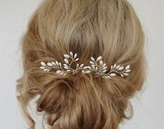 Item # HP-027: This listing is for a set of three (3) only Clear AB Swarovski crystal and pearl branch bridal hair pins. These 3 hair pins are very versatile, they can be placed around the bottom seam of a bun or updo, clustered together, spaced apart, arranged in a row, you are only limited by your imagination! Perfect for any special occasion.    The hair pins pictured have ivory (lt Cream rose) pearls and clear AB crystals with silver wire on gold hair pins. Veil not included.    Off…