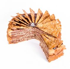 Tort Dobosz Liczne cienkie warstwy chrupiącego ciasta biszkoptowego, przekładane kremem czekoladowym. Udekorowany błyszczącą polewą. Ozdobiony trójkątami krokantu z migdałowych płatków.