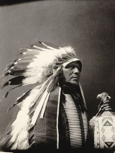 Portrait of Chief of Loafer Band, Ta-Semke-Tokeo, called Paul Strange Horse, in native dress with headdress, breastplate and holding bag. Part of Siouan (Sioux) and Brule Tribes. c. 1907.