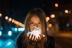 Photo of a girl holding Christmas Fairy Lights on a busy street. Photo by FernandoPB on Twenty20