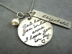 This listing is for a custom hand stamped stainless steel necklace. It is stamped with  God has you in his arms, I have you in my heart. It has a brushed finish with hammered edges. To the side is a hammered rectangle tag stamped with a name. This comes with a freshwater pearl and a stainless steel chain of your choice. We carry petite ball, ball, or cable and can cut them to the length of your choice up to 24.   Please include in the memo to seller at checkout the name or date you would…