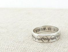The mountains are calling...A simple silver ring with a serene mountain pattern on the exterior and The Mountains Are Calling And I Must Go engraved inside. You