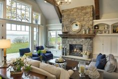 a natural stone fireplace is flanked by a built-in cabinet in one side and by a window seat in the other. Windows frame the stunning view. Inspiring Lake House Interiors Decor Home Living Room, Living Room Furniture Arrangement, Living Room Furniture Layout, Living Room White, Living Room Windows, New Living Room, Living Room Interior, Home And Living, Living Room Designs