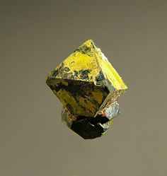 Uraninite, Uranophane (by Fred E. Davis) A cluster of seven crystals (four visible in photo) of Uraninite with a yellow Uranophane coating