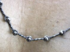 Twisted wire link chain.  Wish Seed.