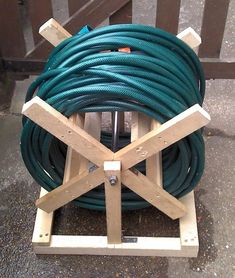 Ideas, Diy Wooden Hose Storage For Garden Appliances Plus Long Blue Hose Ga. Ideas, Diy Wooden Hose Storage For Garden Appliances Plus Long Blue Hose Garden Hose Storages: Useful at Once R Garden Hose Storage, Garden Hose Holder, Garden Hose Reels, Scrap Wood Projects, Woodworking Projects, Water Hose, Wooden Diy, Wood Turning, Garden Tools