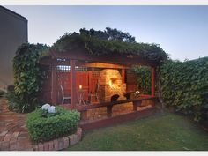 Outdoor fireplace of 2 bedroom brick and cedar 1977 home @ Kelvin Road, Remuera. Original - large brick outdoor fire and wood gazebo on patterned brick paving.   (in Nov 2014)