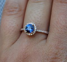 The ring features cornflower blue round sapphire in amazing color, approx. 0.87ct, eye-clean, surrounded by pave set diamonds (SI/I-J), TDW approx.