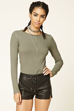 A pair of faux leather shorts featuring a lace-up front and a raw-cut hem.