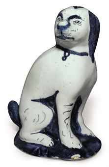 AN ENGLISH BLUE AND WHITE MODEL OF A SEATED HOUND EARLY 18TH CENTURY Modeled seated on its haunches, its features, ears and tail enriched in blue and painted with a collar, on a dark-blue mound base