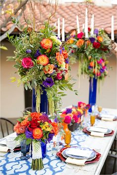 I love the blue vases with the bright colors - don't like the candles and the vases don't need to be as tall, but like the colors here!