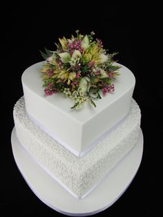 This heart shaped wedding cake is white chocolate mudcake with white chocolate ganache and covered in fondant. The bottom tier is covered in piped chantilly lace and the top tier is left plain and topped with a gorgeous posy of native flowers supplied by Floral Perfection — at Capri Receptions.