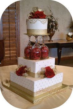 Elegant Ivory and Gold Wedding Cake i like the upside down glasses w/ flowers :] creative